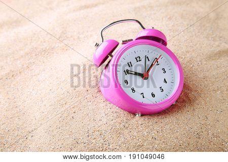 Pink alarm clock on beach sand, close up