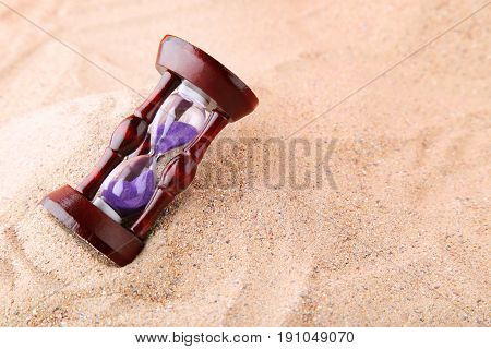 Wooden hourglass on the beach sand, close up