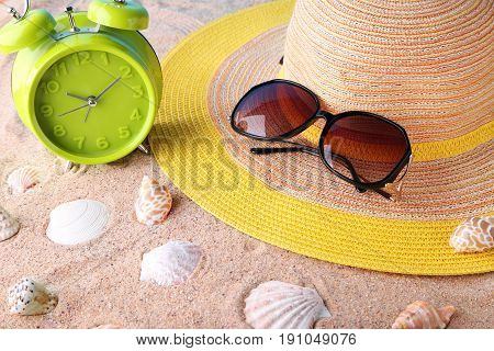 Green Alarm Clock With Sunglasses And Hat On Beach Sand