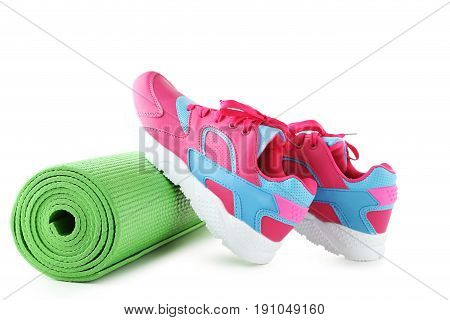 Sport shoes with fitness mat isolated on a white background