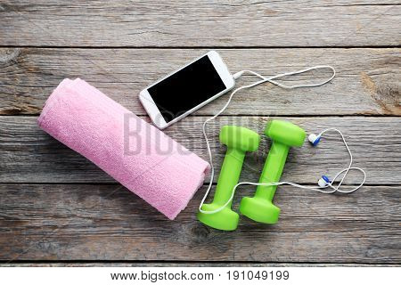 Green dumbbells with towel and smartphone on grey wooden table