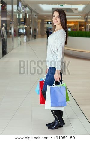 Beautiful Girl Walks In The Mall With Gift Bags.