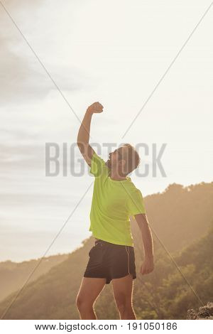 Success of a man after jogging / exercising on a clif near the sea / ocean.