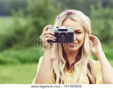 Attractive, young hippie girl taking pictures outdoors at summer. Holiday, vacation, hobby concept.