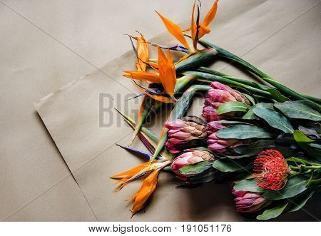 Fresh Real Tropical Flowers on Brown Paper Craft Background