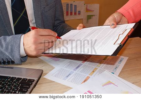Close up of couple signing documents young man putting signature on document. Businessman is signing a contract business contract details