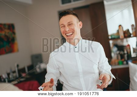 Stylish handsome groom in a white shirt laughing