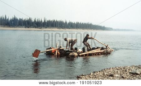Two men rowing down the riveron self-made log raft. Vintage expedition like in old gold rush times. Alaska. Blurry and grainy old-style photography.