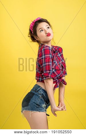 Asian Woman Retro Portrait With Pin-up Make-up And Hairstyle Posing Over Yellow Background.