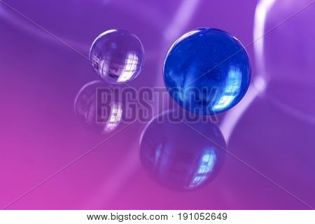 Two beautiful glass ball on a glass table with reflection. Selective focus