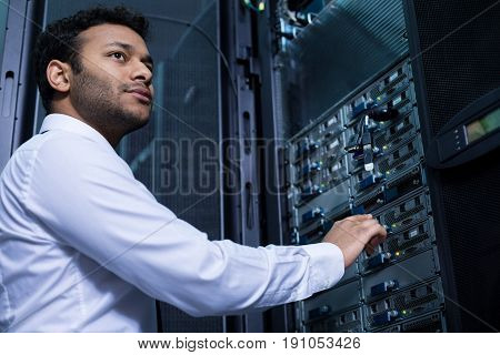 Informational storage. Serious nice young man stretching out his hands and intending to press the button while working with informational technology