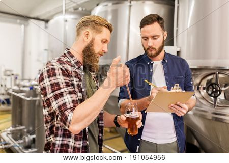 alcohol production, manufacture, business and people concept - men with pipette and clipboard testing craft beer at brewery
