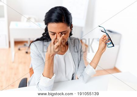 business, overwork, deadline, vision and people concept - tired businesswoman with glasses working at office and rubbing eyes
