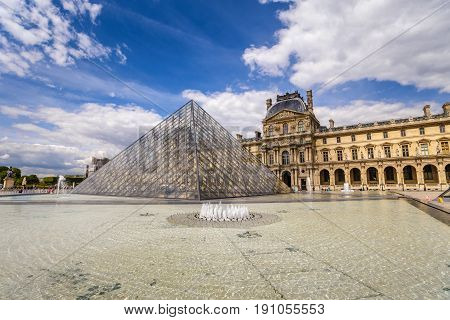 PARIS FRANCE: MAY 2 2017: Sunny day at Louvre Pyramid of Louvre Museum in Paris France