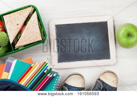 Lunch box with vegetables and sandwich on wooden table. Kids take away food box and school supplies. Top view with blackboard for your text