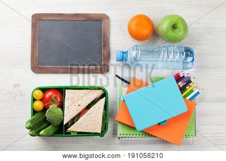 Lunch box with vegetables and sandwich on wooden table. Kids take away food box and school supplies. Top view with copy space