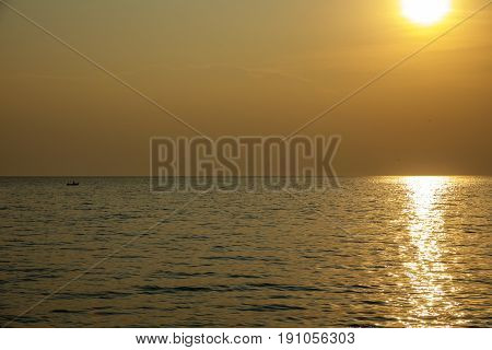 Long shot of small boat arriving to coast at sunset
