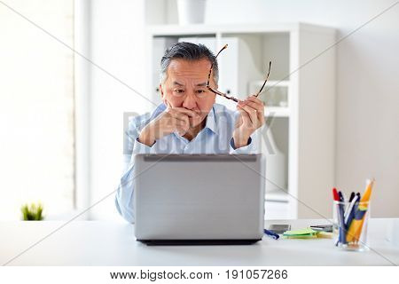 business, deadline, stress, people and technology concept - businessman with eyeglasses and laptop computer at office