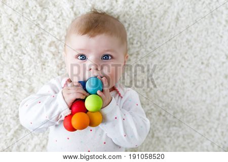 Cute adorable newborn baby playing with colorful wooden rattle toy ball on white background. New born child, little girl looking at the camera. Family, new life, childhood, beginning concept