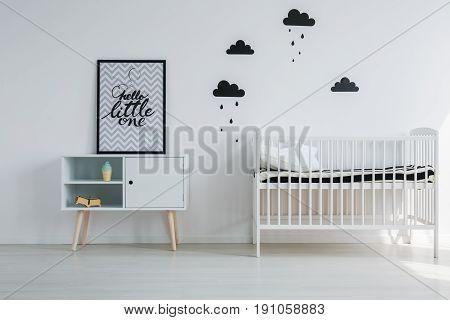 Sweet monochromatic nursery with cupboard in vintage style