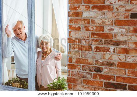 Senior smiling elegant couple looking through window in apartment