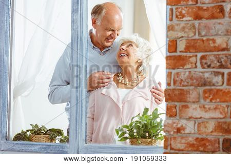 Elderly man embracing smiling woman by the window