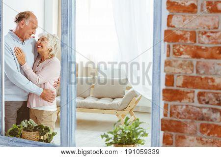 Senior happy elegant couple hugging in stylish apartment