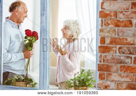Elderly elegant man giving smiling surprised woman roses