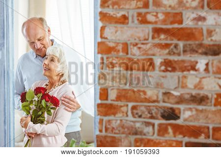 Happy elegant woman holding roses while being embraced by smiling man