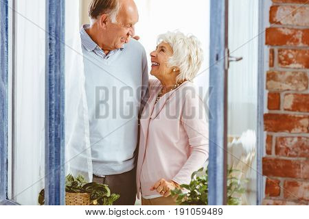 Senior happy couple laughing by the window at home