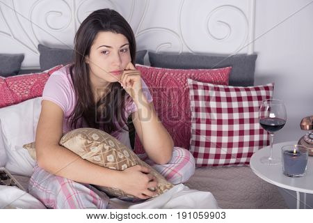 Pensive woman with wine during lonely evening in bed