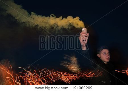 Soccer fan with smoke bomb. Rowdy guy with protest sign in hand on night lights background.