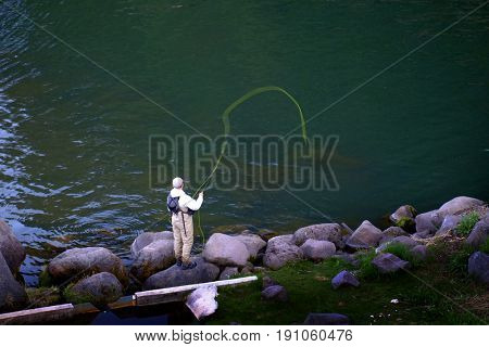 Person fishing in stream or river in wilderness for sport
