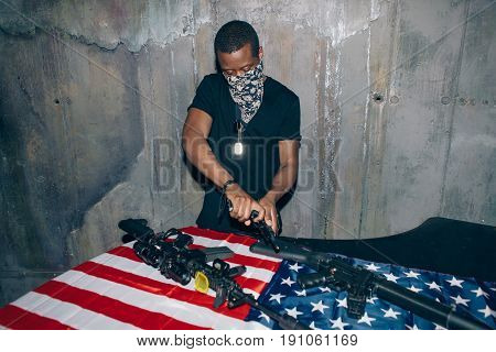 Black gun dealer checks a weapon. Mercenary man with gun in hand on dark gray background. Outlaw, ghetto, social problem, armed attack concept poster