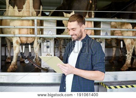agriculture industry, farming, people, milking and animal husbandry concept - young man or farmer with clipboard and cows at rotary parlour system on dairy farm