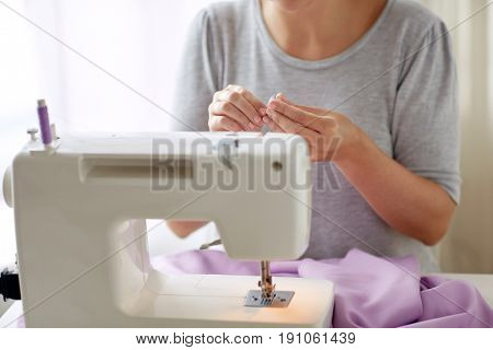 people, needlework and tailoring concept - tailor woman with spool of thread and sewing machine at studio