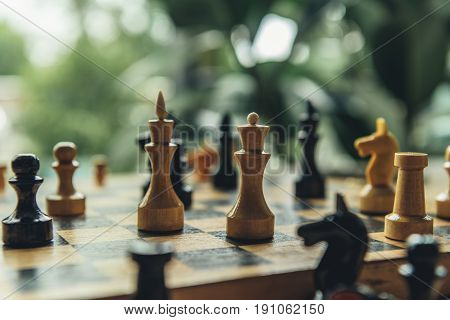Closeup View Of Black And White Chess Figures On Chess Board. Focus On Foreground With White King An
