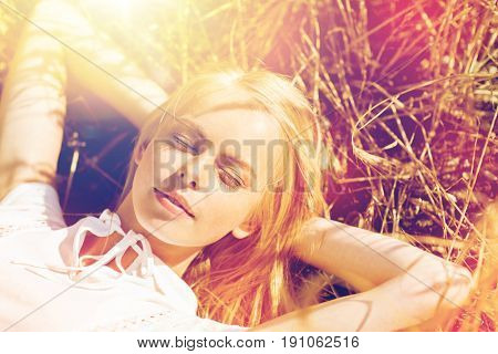 nature, summer holidays, vacation and people concept - happy young woman lying and enjoying sun on cereal field or hay