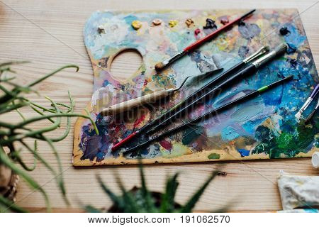 High Angle View Of Artist Palette With Paint Brushes And Palette Knife On The Top