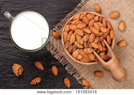 Almond milk in a glass and almonds in wooden bowl on black stone background. Top view.