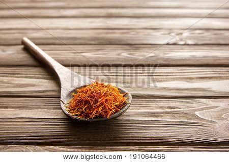 Spice saffron in wooden spoon on wooden table. Close-up.