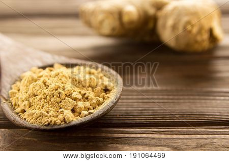 Ginger powder in wooden spoon on wooden table. Close-up.