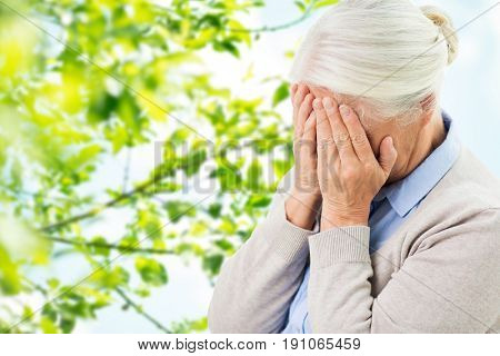 stress, age and people concept - senior woman suffering from headache or grief over green natural background