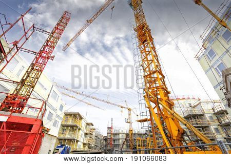wide view of construction site, cranes and scaffolding