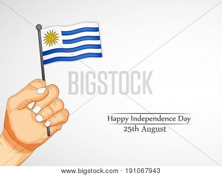 illustration of a hand holding Uruguay flag with Happy Independence Day 25th August Text