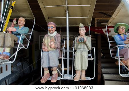 Funny Wooden People Sitting On Ski Chair-lift. Souvenirs For Sale At Gift Store In Grindelwald Villa