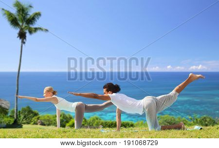 fitness, sport and people concept - couple making yoga balancing table pose outdoors over exotic natural background with palm tree and ocean