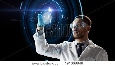 science, research and people concept - young scientist in safety glasses with test tube and virtual projection
