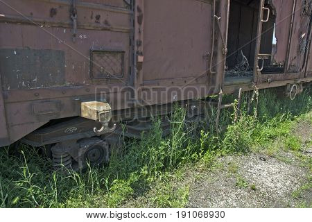 Old railway wagon on the railway track in the weeds bushes and grass.