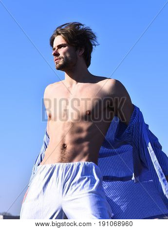 Bearded man short beard. Caucasian macho with moustache and ruffled hair in blue striped pajamas showing strong torso with six packs on blue sunny sky background